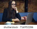 pensive young female freelancer ... | Shutterstock . vector #716952286