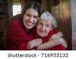 an elderly woman in an embrace... | Shutterstock . vector #716953132