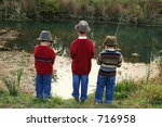 Three brothers fishing on the riverbank wearing grandfather