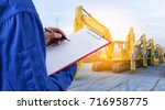 Worker checking document in front of the mechanical excavator at yard  for import export business. - stock photo