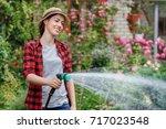 happy young woman gardener watering garden with hose. Hobby concept