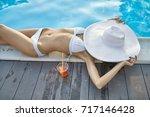 fancy girl in a white swimsuit...   Shutterstock . vector #717146428
