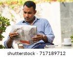 serious man reading newspaper... | Shutterstock . vector #717189712