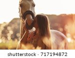 Stock photo woman kissing her horse at sunset autumn outdoors scene 717194872
