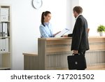 young female receptionist... | Shutterstock . vector #717201502