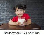 asian little girl drinking a... | Shutterstock . vector #717207406