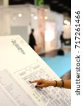 Small photo of Business woman hand showing on a map at a trade fair