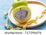 diet slimming. green apple with ... | Shutterstock . vector #717296476