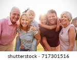 Small photo of Multi generation family in garden smile to camera, close up