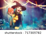 Stock photo halloween witch with a carved pumpkin and magic lights in a dark forest beautiful young surprised 717305782