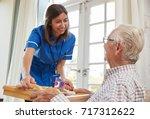nurse serving dinner to a...   Shutterstock . vector #717312622