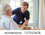 male care worker serving dinner ... | Shutterstock . vector #717312628