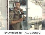happy adult guy is listening to ... | Shutterstock . vector #717330592