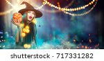 Stock photo halloween witch with a carved pumpkin and magic lights in a dark forest beautiful young surprised 717331282