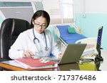 doctor working with laptop... | Shutterstock . vector #717376486