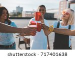 group of friends clinking glasses on alcohol on roof party - stock photo