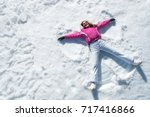 Small photo of High angle view of happy woman lying on snow and moving her arms and legs up and down creating a snow angel figure. Smiling woman lying on snow in winter holiday with copy space.