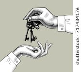 a man's hand gives the keys to... | Shutterstock .eps vector #717434176