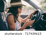woman using mobile phone while... | Shutterstock . vector #717439615