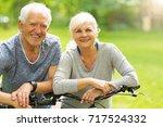 senior couple riding bikes in... | Shutterstock . vector #717524332