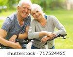 senior couple riding bikes in... | Shutterstock . vector #717524425