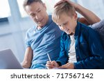 proud father patting son on the ... | Shutterstock . vector #717567142