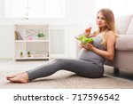 young pregnant woman eating... | Shutterstock . vector #717596542