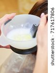 Small photo of Hands mixing hair dye. Bowl with hair dye, macro.