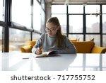 pensive female student doing... | Shutterstock . vector #717755752