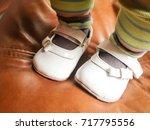 baby girl feet wearing white... | Shutterstock . vector #717795556