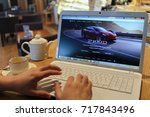 Small photo of MOSCOW, RUSSIA - SEP 16, 2016: mans hands keyboarding on laptop computer in cafe room, Tesla auto dealer website on monitor, closeup