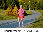 woman running in autumn park ... | Shutterstock . vector #717933256