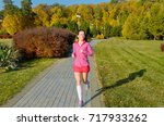 woman running in autumn park ... | Shutterstock . vector #717933262