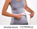 happy fitness girl measuring... | Shutterstock . vector #717999412