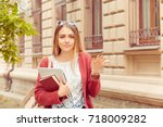 Small photo of Confused student. Closeup portrait puzzled clueless young woman arm out asking what is problem who cares so what I don't know isolated college building on background. Negative emotion face expression