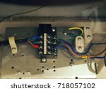 Small photo of Old electronic electrical CLN fuse with power cords connected with screw, on aluminum steel board under air conditioner circuit cabinet, with dust and dirty human hair