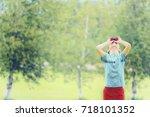 boy looks up through binoculars.... | Shutterstock . vector #718101352