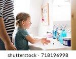 little girl in bathroom with... | Shutterstock . vector #718196998
