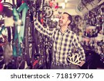 young man selects bicycle in... | Shutterstock . vector #718197706