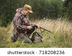 Small photo of Hunter with a backpack and a hunting gun in the autumn forest. Man is charging a hunting rifle.