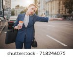 Small photo of oung stylish businesswoman with coffee cup catching a taxi. Woman doing multiple tasks. Multitasking business woman.