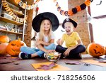 Small photo of Treat or trick! dessert! Cheerful amazed excited small kids in carnival head wear, with colorful treats, carved pumpkins, fall leaves, orange papers near them, sit on the brown wooden floor at home
