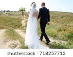 happy bride and groom holding...   Shutterstock . vector #718257712