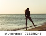 woman is alone at beach   Shutterstock . vector #718258246