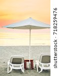 two sun beds and an umbrella on ...   Shutterstock . vector #718259476