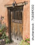 Small photo of Old faded wooden door with metal overhead lantern and southwest Adobe orange clay walls.