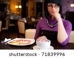 girl sitting in cafe with cup of coffee and food - stock photo