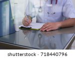 doctor writing a medical... | Shutterstock . vector #718440796