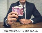 a businessman giving money in...   Shutterstock . vector #718546666