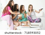young women watching tv at home   Shutterstock . vector #718593052